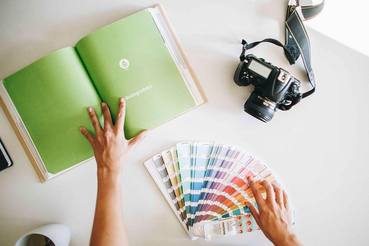 Uxia de Meraki ojeando el libro eco packaging now, diseñadora gráfica sostenible